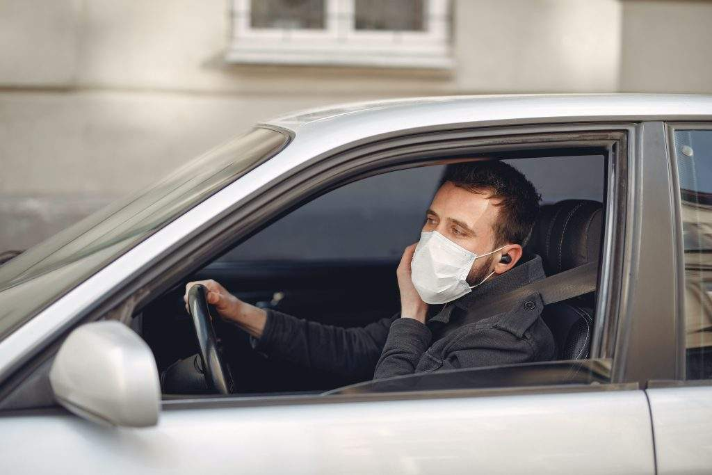 man driving car with face mask